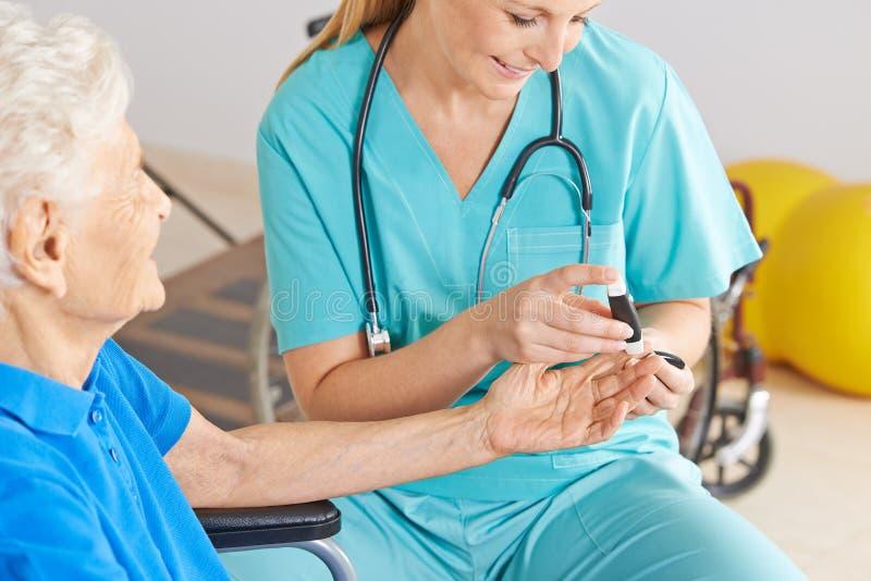 Geratric nurse monitoring blood sugar. Of senior women with diabetes stock photo
