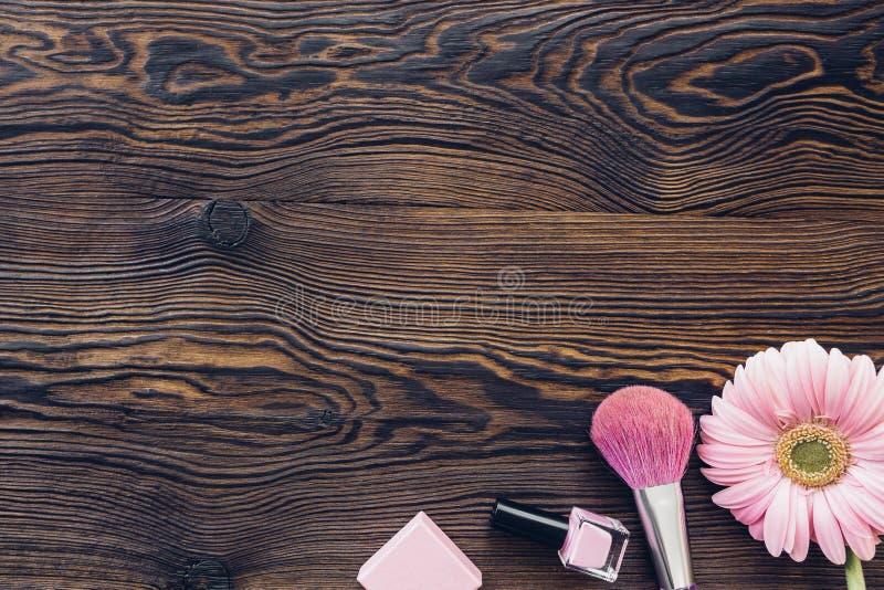 Gerbera rosado, cepillo del maquillaje, esmalte de uñas en el fondo de madera, visión superior Espacio para el texto fotografía de archivo