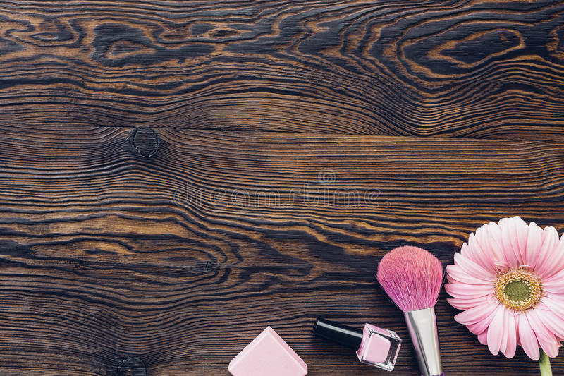 Gerbera rose, brosse de maquillage, vernis à ongles sur le fond en bois, vue supérieure L'espace pour le texte photographie stock