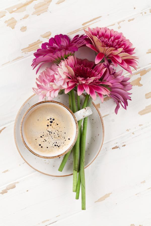 Gerberaen blommar bukett- och kaffekoppen royaltyfri bild