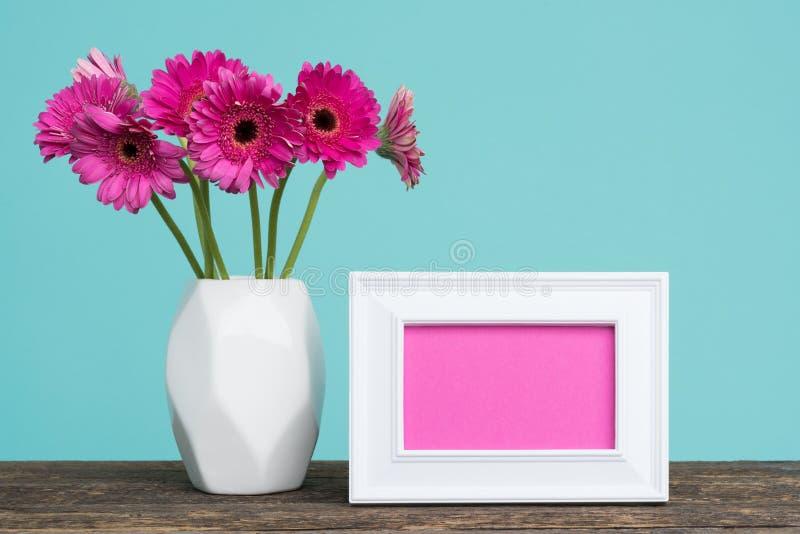 Gerberas cor-de-rosa escuros em um vaso em uma tabela com o cartão vazio da moldura para retrato imagem de stock
