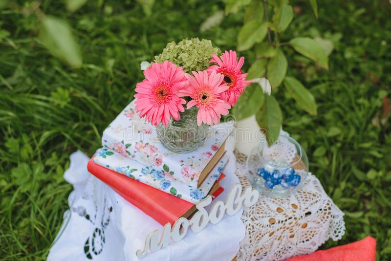 Gerberas in a vase standing on a stack of books next to the word in the Russian language `love stock image