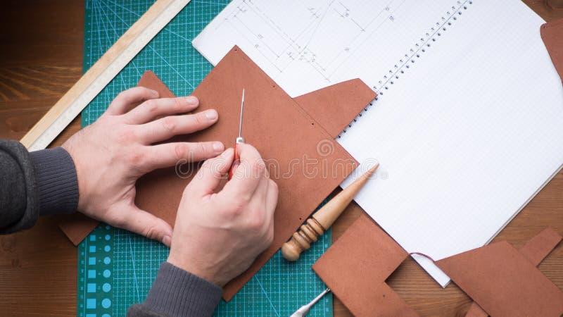 Gerberhände bei der Arbeit mit Ahle, Regenjacke und Leder Vorgewählter Fokus, Abschluss oben lizenzfreie stockfotografie