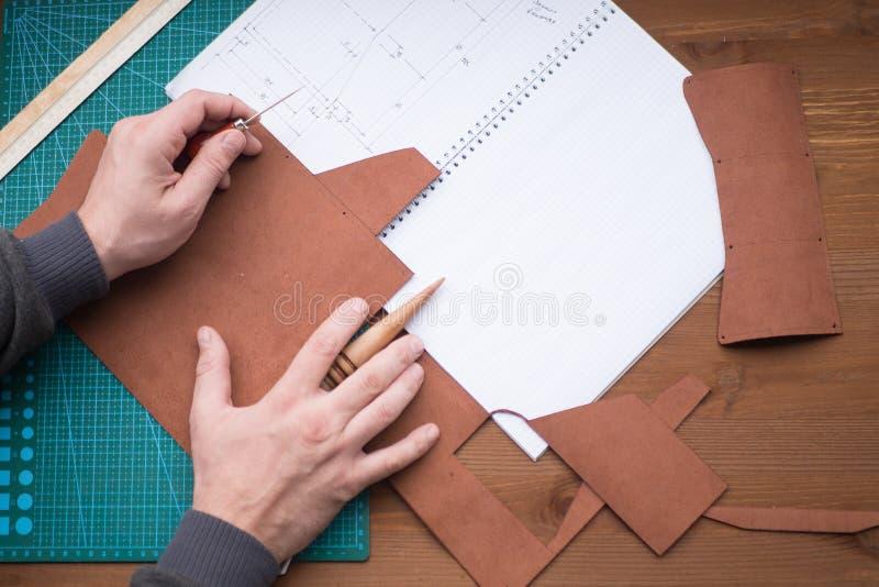 Gerberhände bei der Arbeit mit Ahle, Regenjacke und Leder Vorgewählter Fokus, Abschluss oben stockfoto