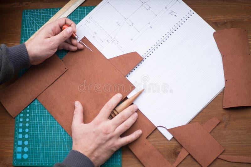 Gerberhände bei der Arbeit mit Ahle, Regenjacke und Leder Vorgewählter Fokus, Abschluss oben stockfotografie