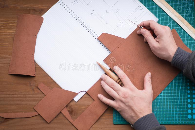 Gerberhände bei der Arbeit mit Ahle, Regenjacke und Leder Vorgewählter Fokus, Abschluss oben stockfotos
