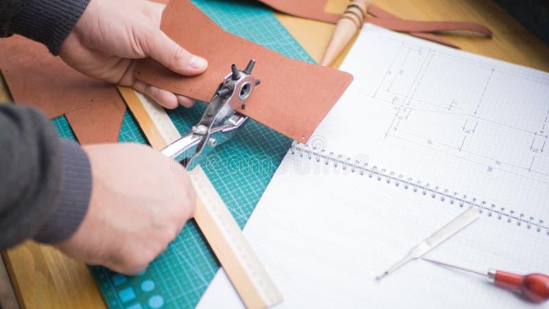 Gerberhände bei der Arbeit mit Revolverdurchschlag, -ahle und -leder Vorgewählter Fokus, Abschluss oben lizenzfreie stockbilder