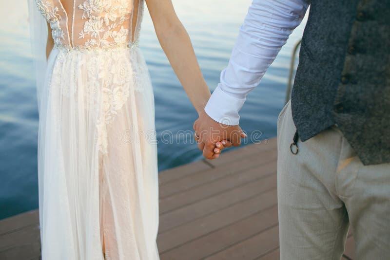 Gerechte Stellung des verheirateten Paars im Naturhändchenhalten und Betrachten der schönen Ansicht von Fluss Genießen an jedem M stockbild