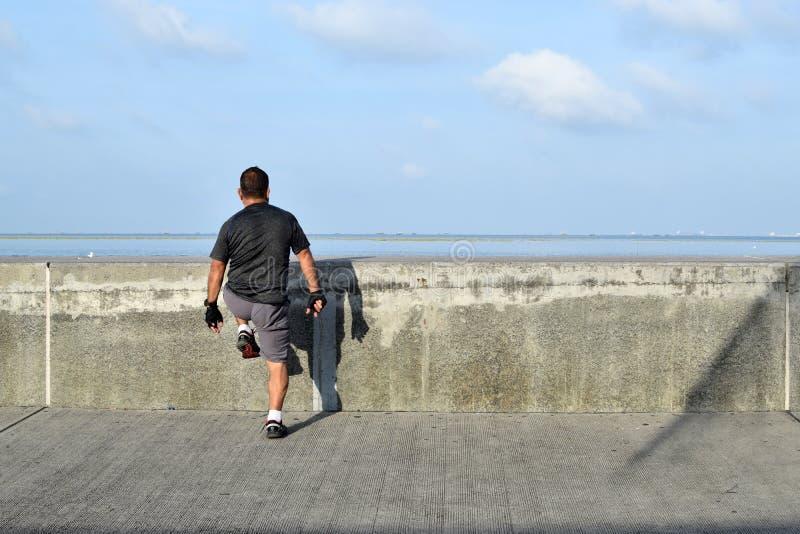 Gereifter Mann, der Übung entlang Ozeanbucht-Bruchwasser ausdehnend tut stockfotos