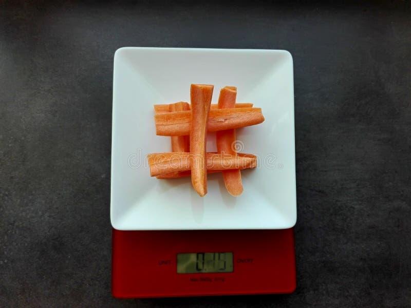 Gereinigte Karotten auf elektronischen Skalen lizenzfreie stockbilder