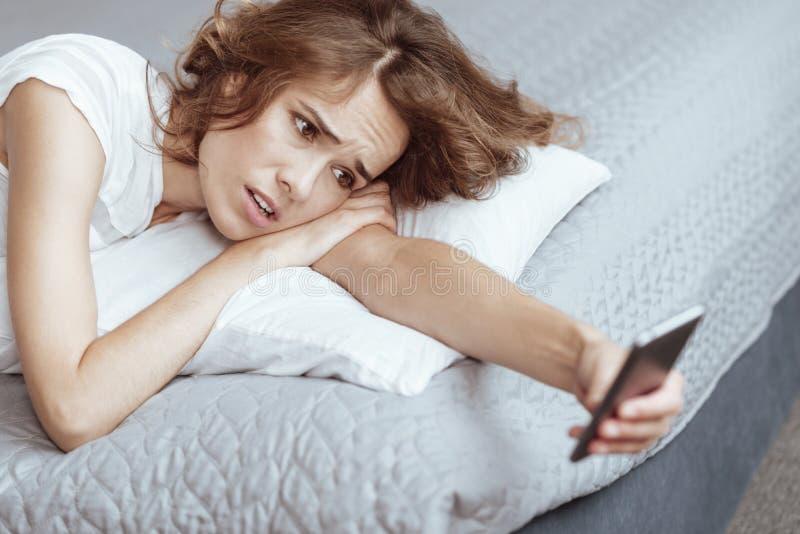 Gereizte reife Dame, die beim Betrachten des Telefons niedergedrückt erhält lizenzfreies stockbild