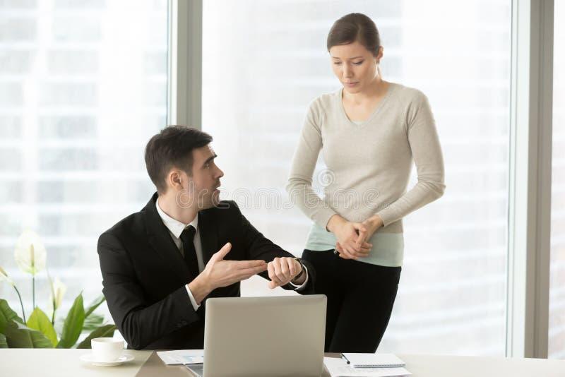 Gereizter Chef, der auf Armbanduhr während nervöser Angestellter mak zeigt stockbilder