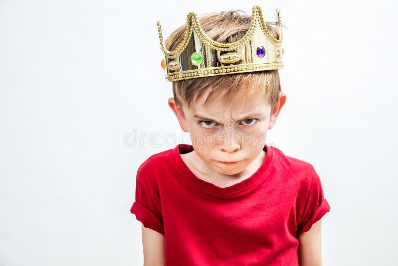 Gereizter schöner verdorbener Junge mit giftigem Blick und goldener Krone stockfoto