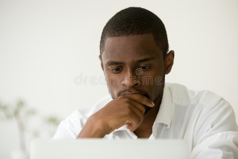 Gerente africano focalizado que trabalha no portátil que pensa do problema assim fotos de stock