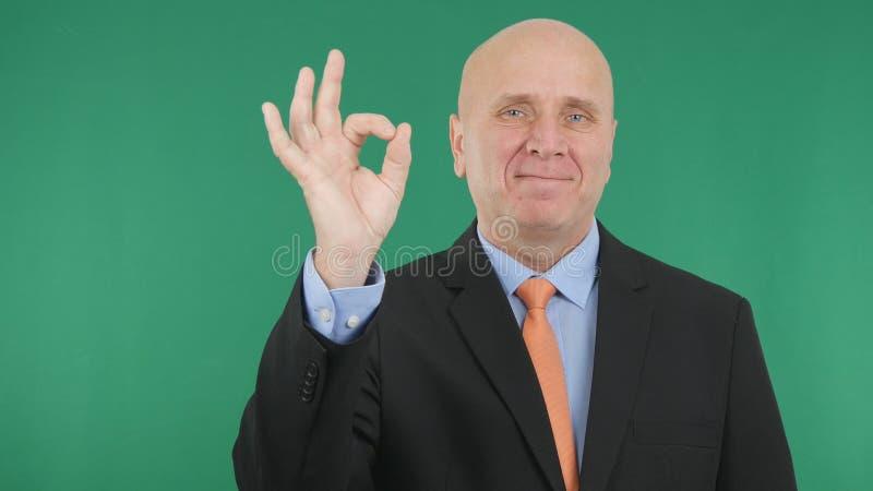 Gerente apresentável Smile e para fazer gestos de mão da APROVAÇÃO fotografia de stock