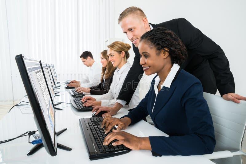 Gerente Assisting His Staff no escritório imagem de stock royalty free