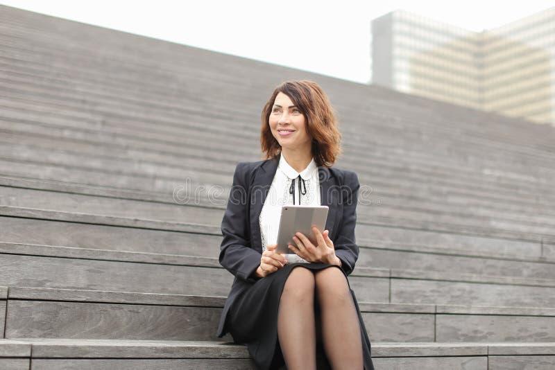 Gerente caucasiano fêmea que senta-se em escadas com tabuleta e trabalho fotos de stock