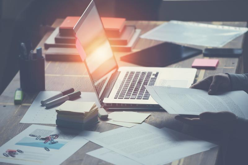 Gerente com o computador e o documento que sentam-se em sua mesa no escritório Dia de trabalho geral fotografia de stock