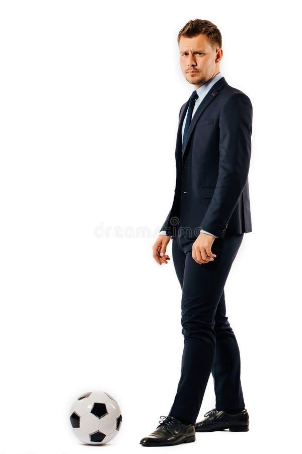 Gerente considerável novo do homem de negócios que retrocede uma bola de futebol no fundo branco isolado fotografia de stock royalty free