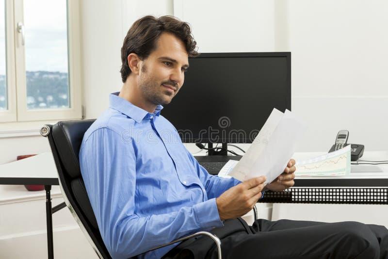 Gerente considerável novo que senta-se em sua mesa no escritório imagem de stock