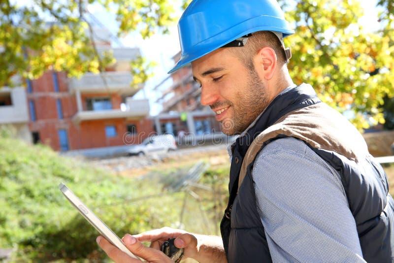Gerente da construção no terreno de construção com tabuleta imagem de stock royalty free