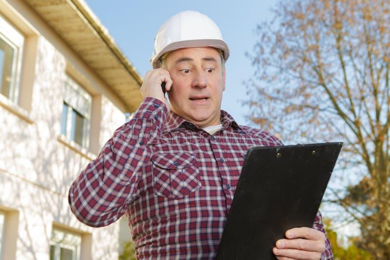 Gerente da construção que dá a informação no custo da avaliação fotografia de stock royalty free