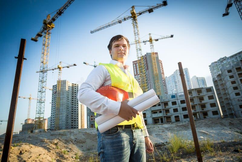 Gerente da construção que levanta no terreno de construção no dia ensolarado foto de stock
