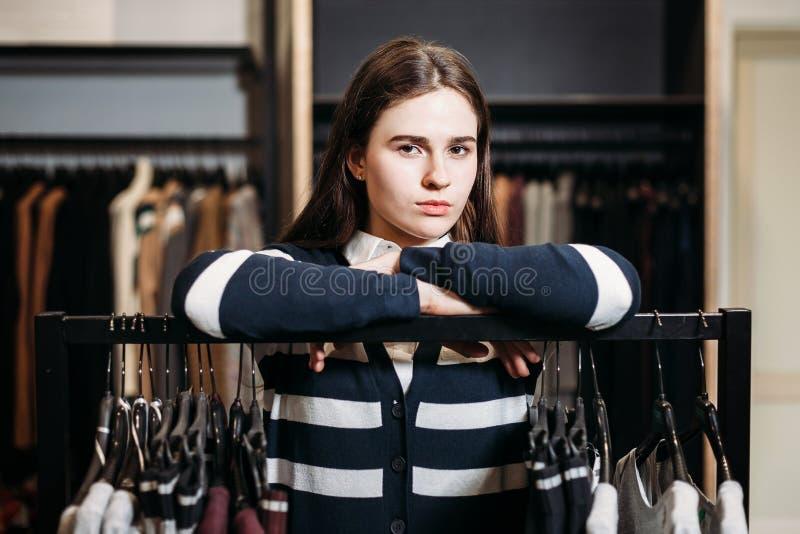 Gerente da loja da jovem mulher perto da cremalheira com ganchos imagem de stock royalty free