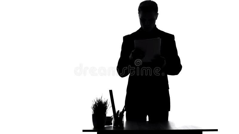 Gerente de empresa que lê atentamente papéis no lugar de trabalho, relatório comercial anual imagem de stock royalty free