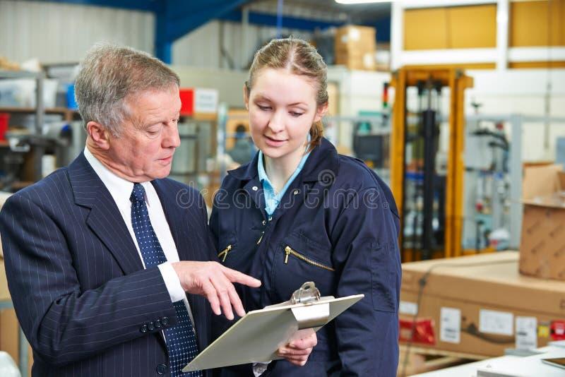 Gerente de fábrica And Apprentice Engineer que olha a prancheta imagem de stock royalty free