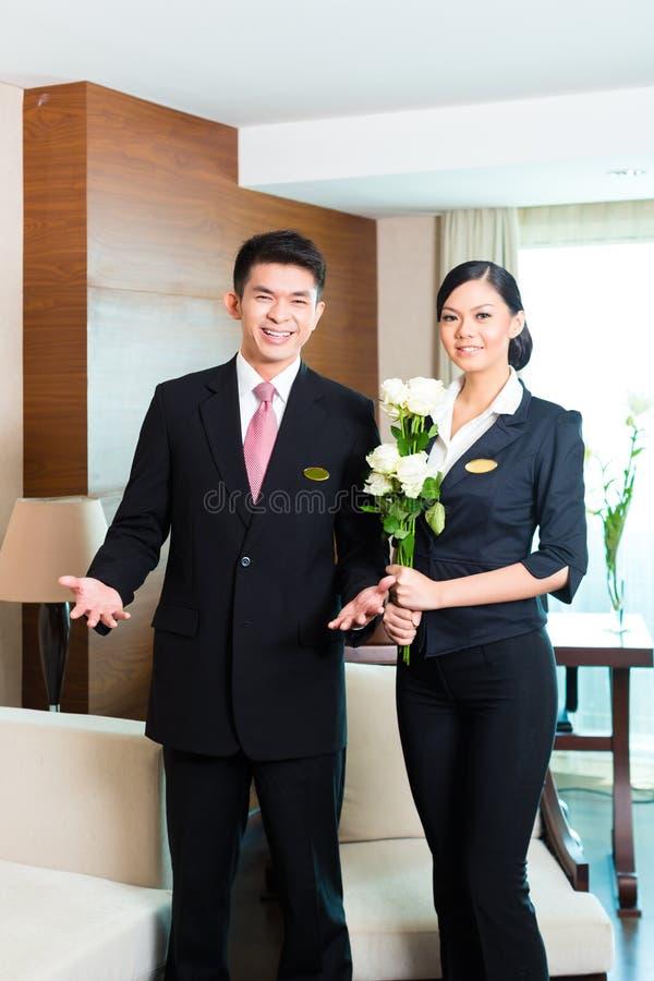 Gerente de hotel chinês asiático que dá boas-vindas a convidados do VIP foto de stock royalty free