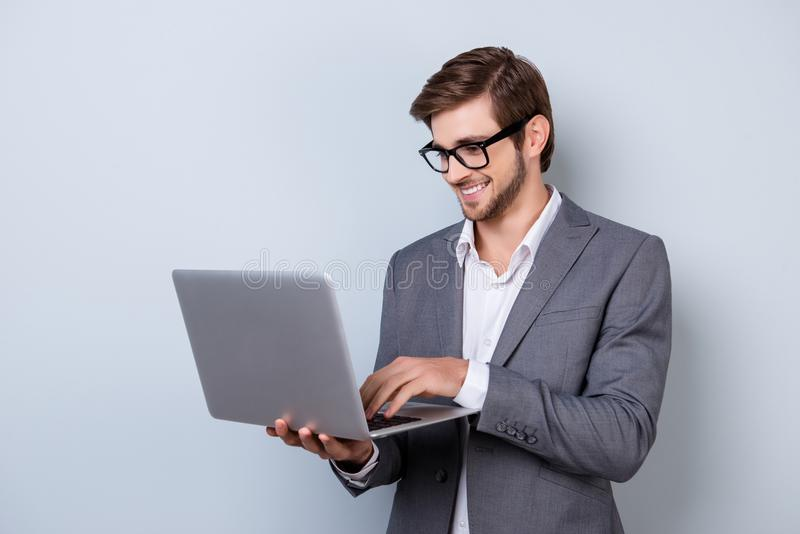 Gerente de sorriso considerável novo no terno que guarda o portátil e o chatti imagem de stock