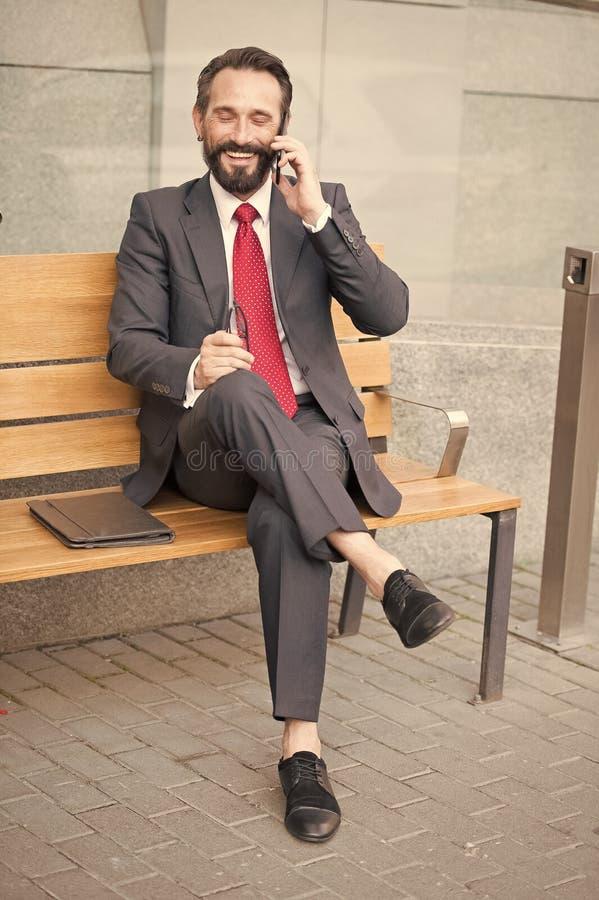 Gerente de sorriso que senta-se no banco e em telefonar Situação nova sorrida considerável do homem de negócios no banco com seu  imagem de stock