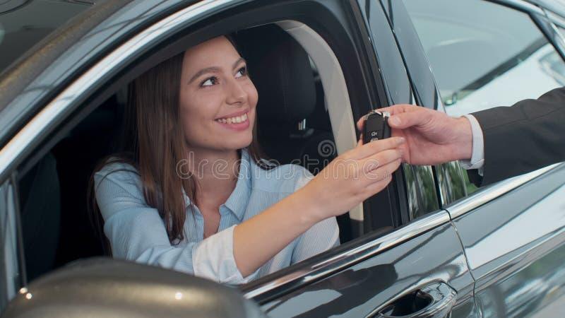 Gerente de vendas que cede as chaves ? menina esse assento no carro foto de stock
