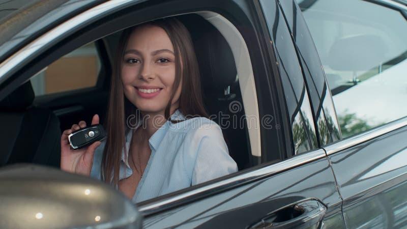 Gerente de vendas que cede as chaves ? menina esse assento no carro imagem de stock