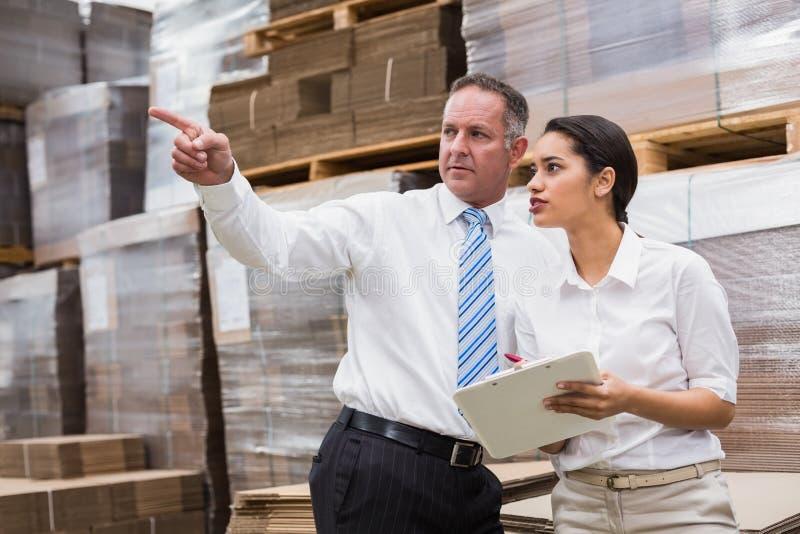 Gerente do armazém e seu chefe que verificam o inventário imagens de stock