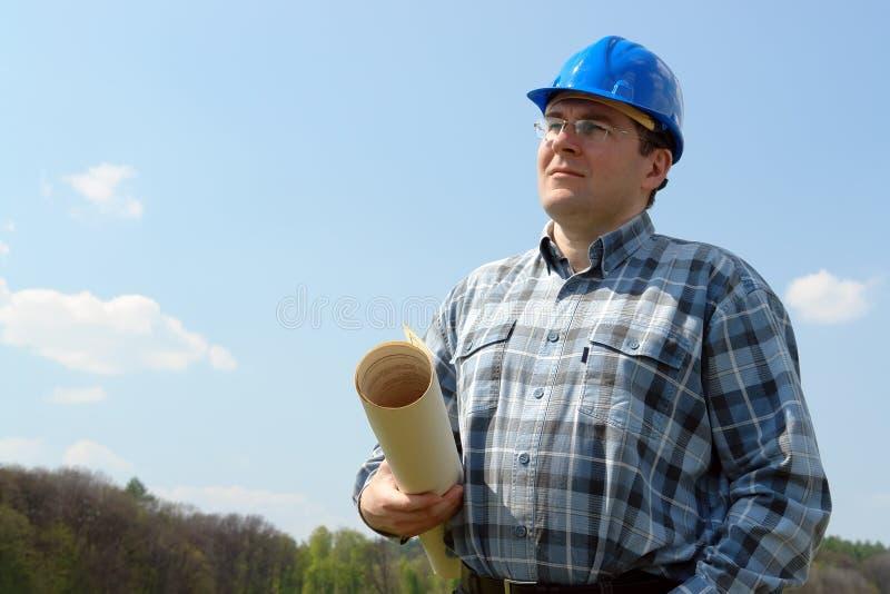 Gerente do canteiro de obras com plantas do edifício foto de stock