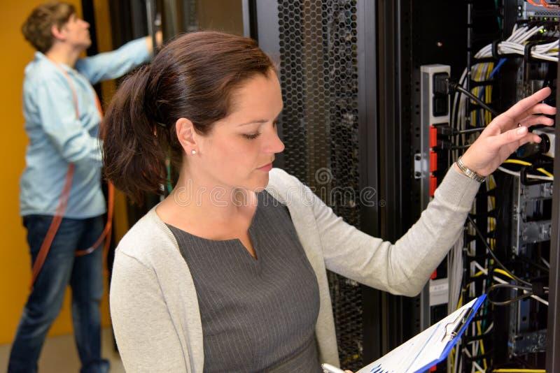 Gerente do datacenter da mulher na sala do servidor imagens de stock