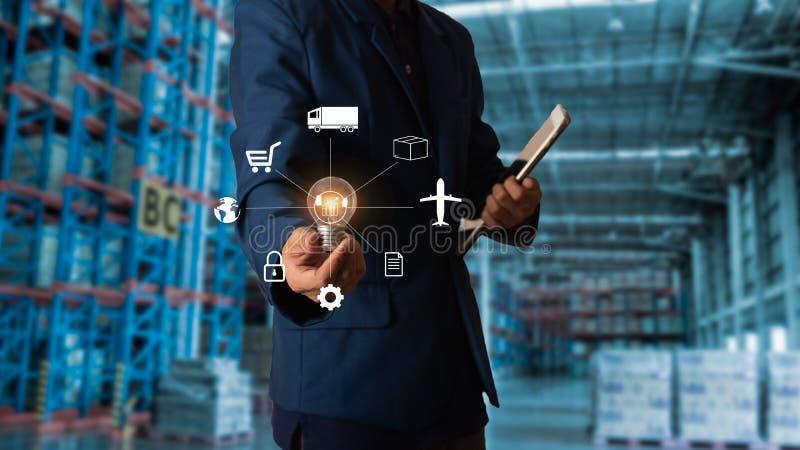 Gerente do homem de negócios que toca no ícone para a logística no armazém de comércio moderno imagem de stock