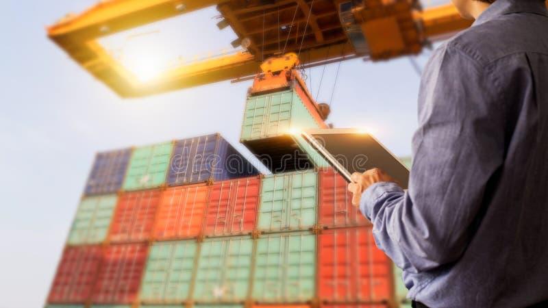 Gerente do homem de negócios que usa a verificação da tabuleta e o controle do recipiente foto de stock
