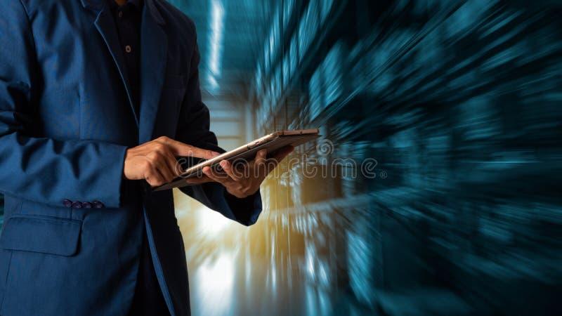 Gerente do homem de negócios que usa a verificação e o controle da tabuleta para trabalhadores com o armazém de comércio moderno fotos de stock royalty free