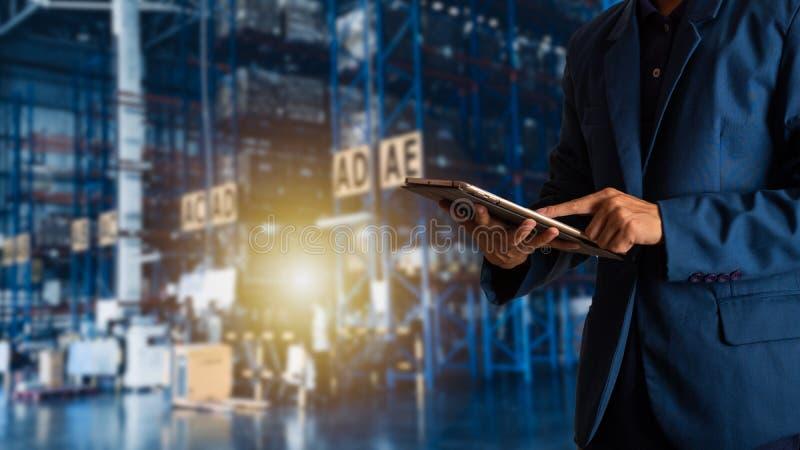 Gerente do homem de negócios que usa a verificação e o controle da tabuleta para trabalhadores com o armazém de comércio moderno imagem de stock