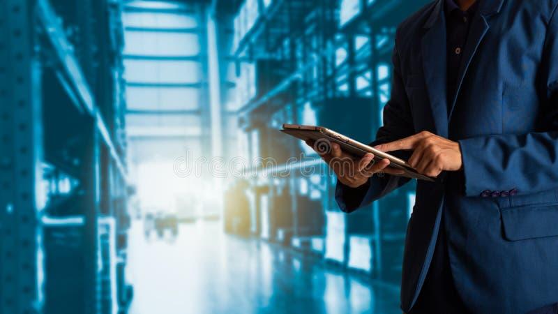 Gerente do homem de negócios que usa a verificação e o controle da tabuleta para trabalhadores com o armazém de comércio moderno imagens de stock