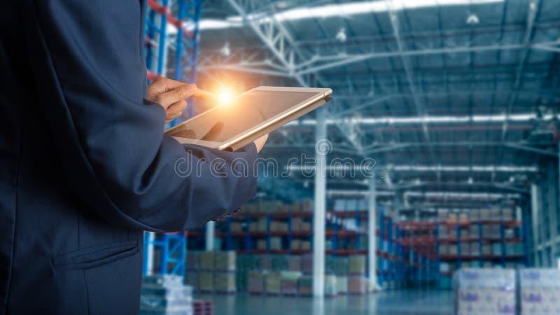 Gerente do homem de negócios que usa a verificação e o controle da tabuleta para trabalhadores com logísticas de comércio moderna foto de stock