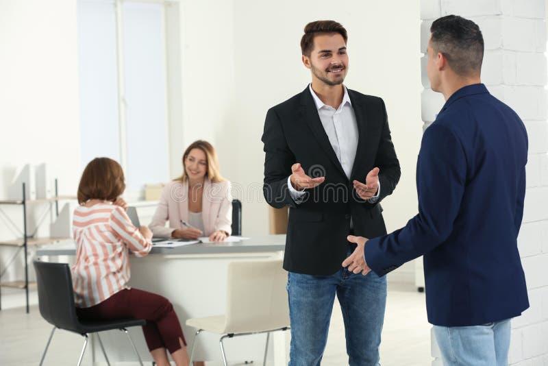Gerente dos recursos humanos que fala com o candidato antes da entrevista de trabalho fotos de stock royalty free