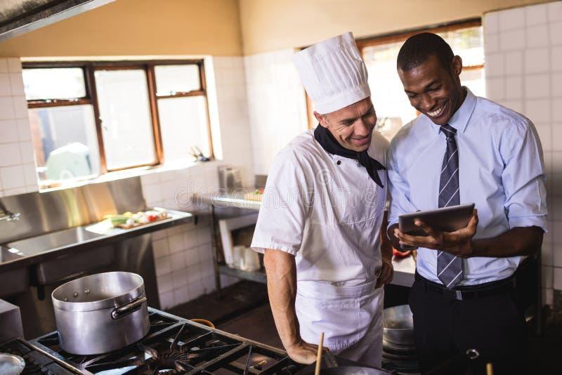 Gerente e cozinheiro chefe masculinos que usa a tabuleta digital na cozinha imagem de stock