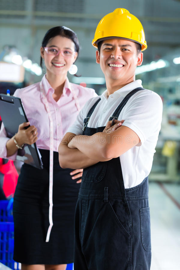 Gerente e desenhista de produção na fábrica asiática imagem de stock