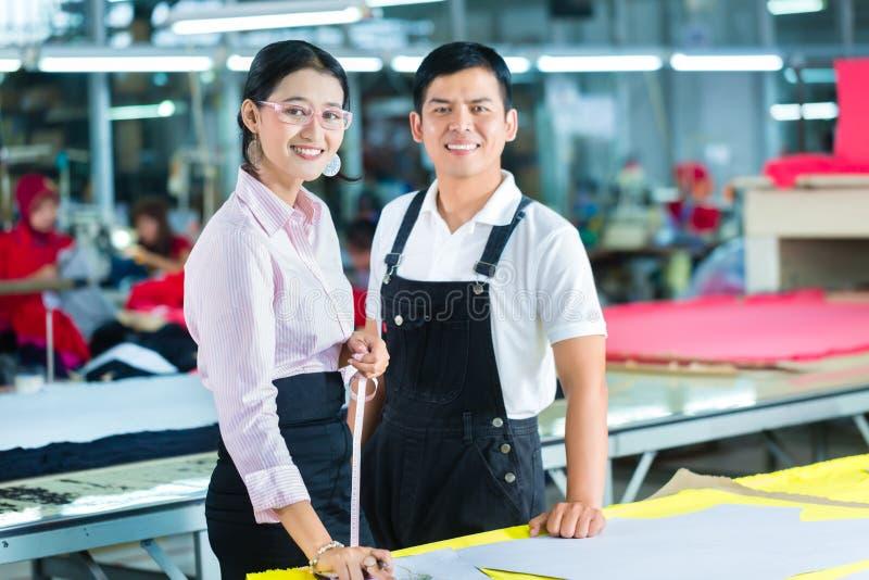 Gerente e desenhista de produção na fábrica asiática foto de stock