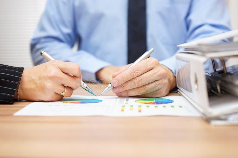 Gerente e mulher de negócio que consulta sobre relatórios de vendas imagem de stock