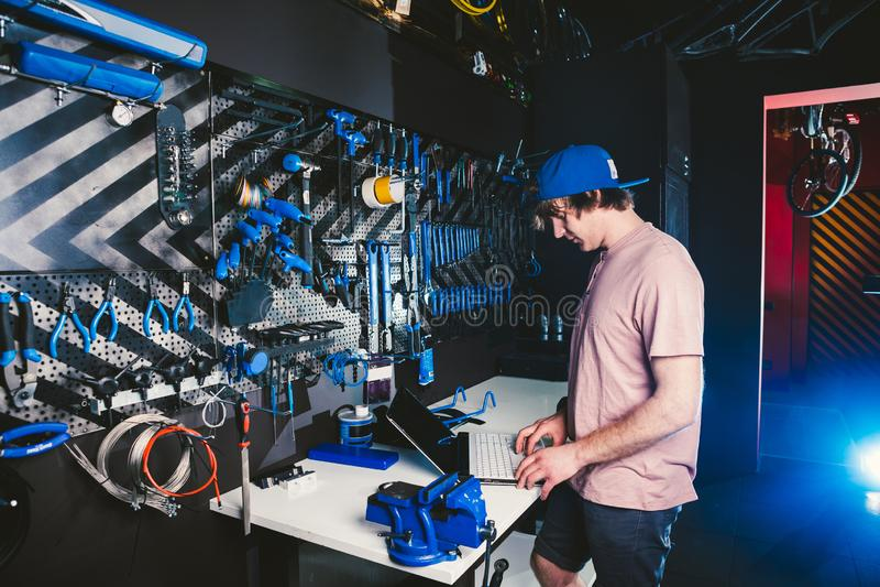 Gerente e tecnologia da profissão do negócio do tema A loja masculina caucasiano à moda nova da bicicleta do proprietário usa um  imagens de stock